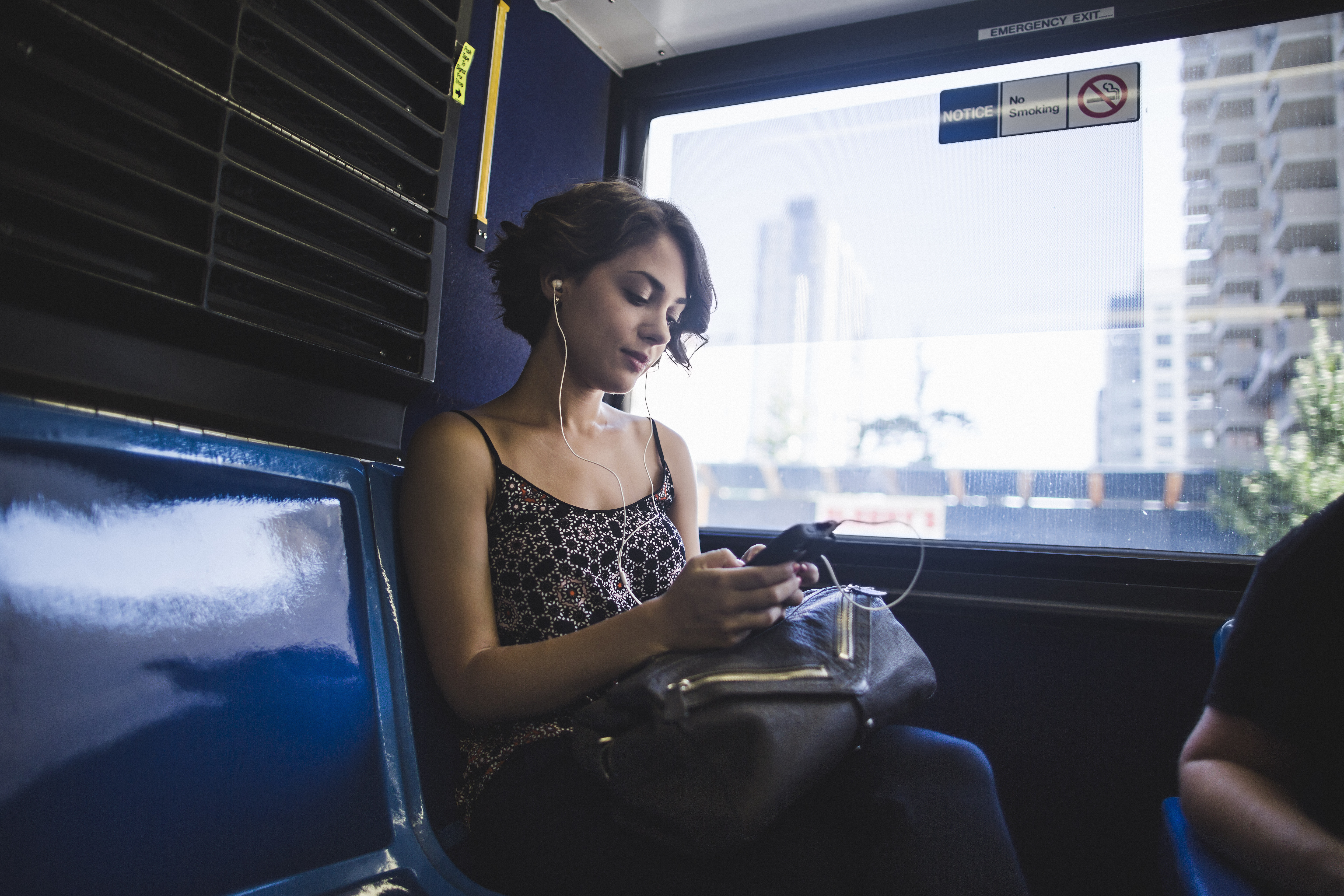 Young woman commuting on bus listening to music on smartphone. (Getty Images)