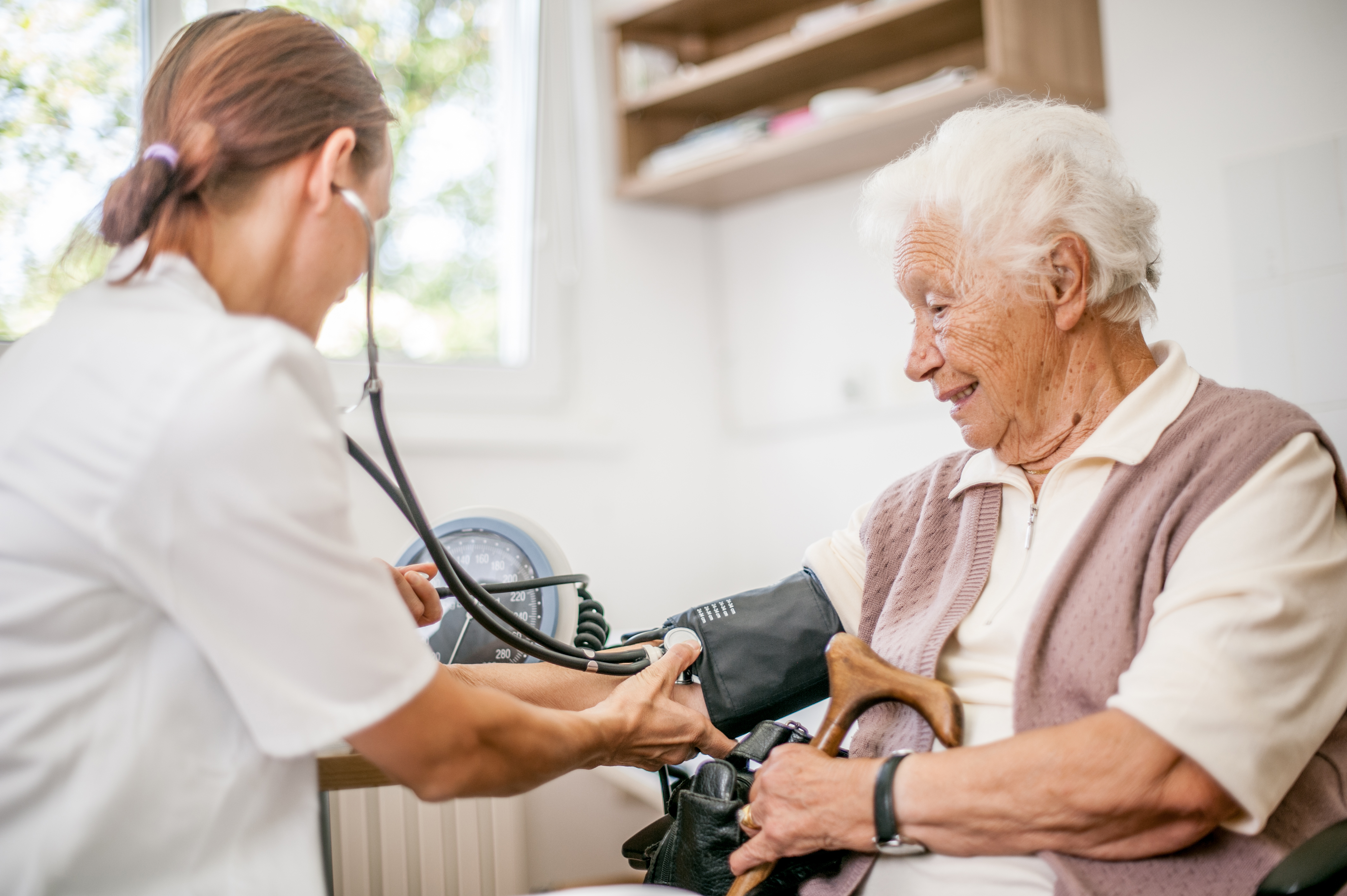 Doctor checks the blood pressure of a senior woman.