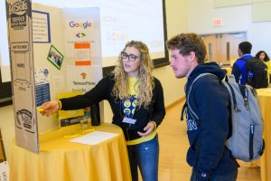 A young woman shows a student a display about artificial intellligence at an innovation event