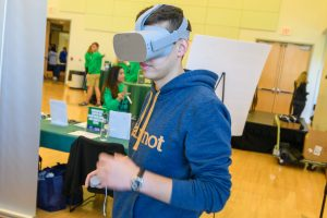 A young man wears a VR headset as part of an innovation event