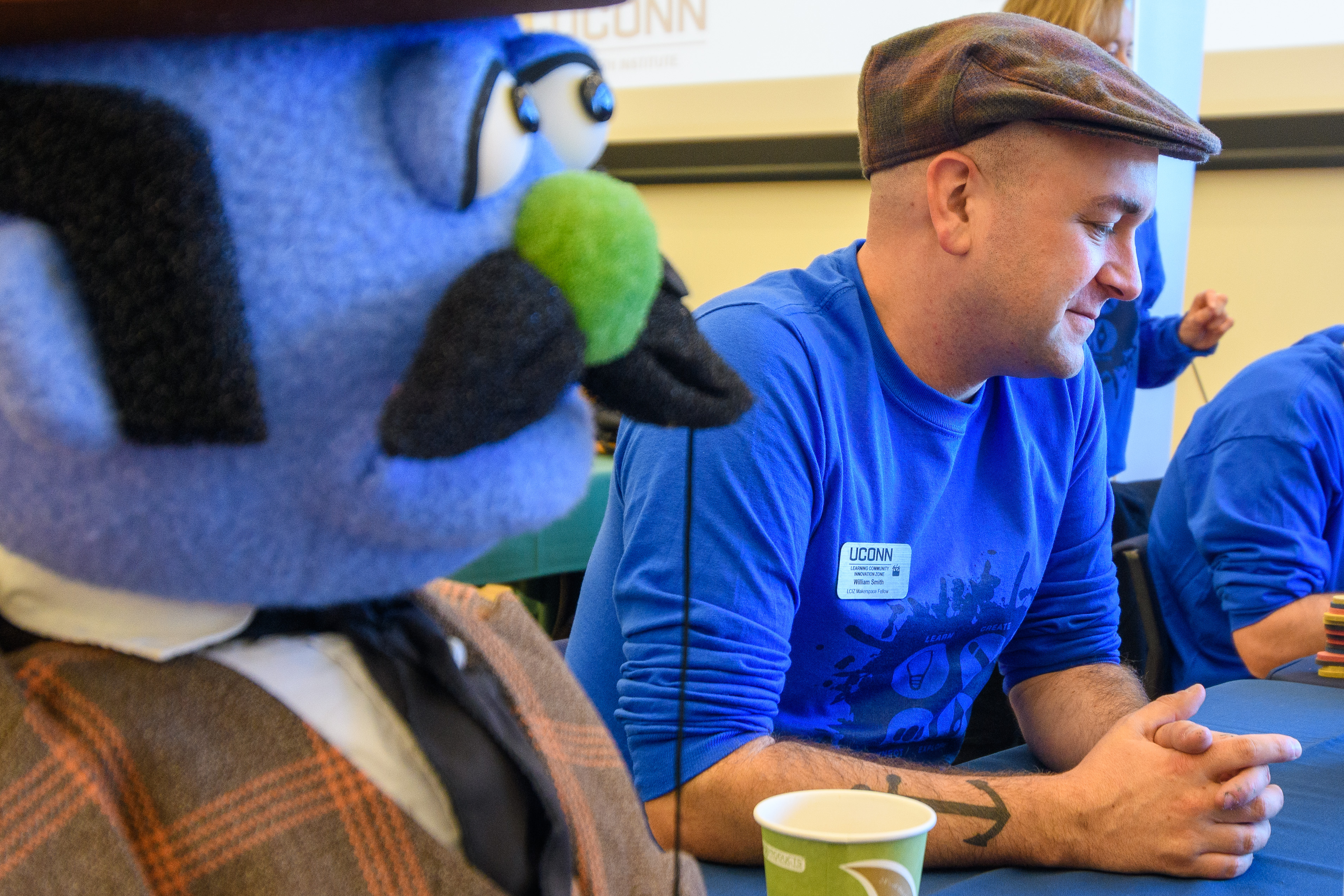 A man sits next to a large blue puppet with a mustache and tie, as part of an innovation event