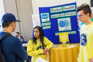A young woman in front of a display on global health talks with attendees at the UConn Innovation Expo