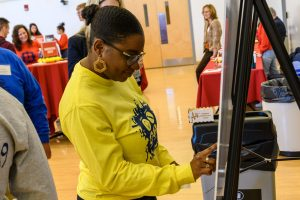 A young woman uses a touchscreen display during an innovation event