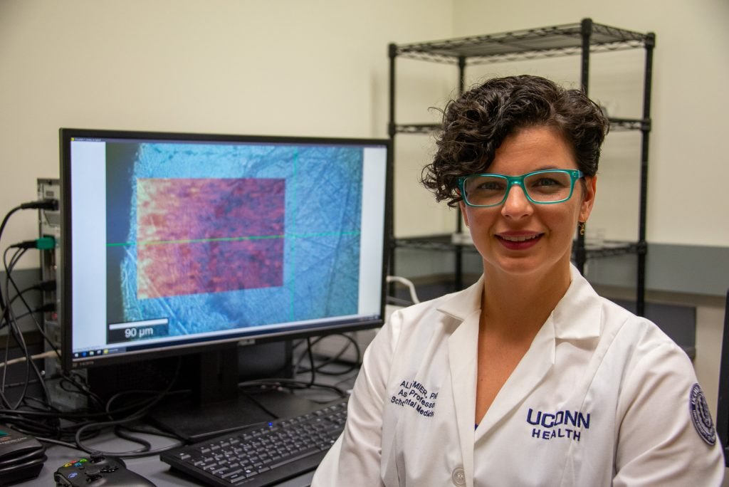 a woman in a white lab coat poses before a computer modeling bone research