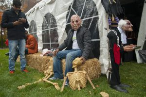 Students in scary Halloween masks gather outside a tent
