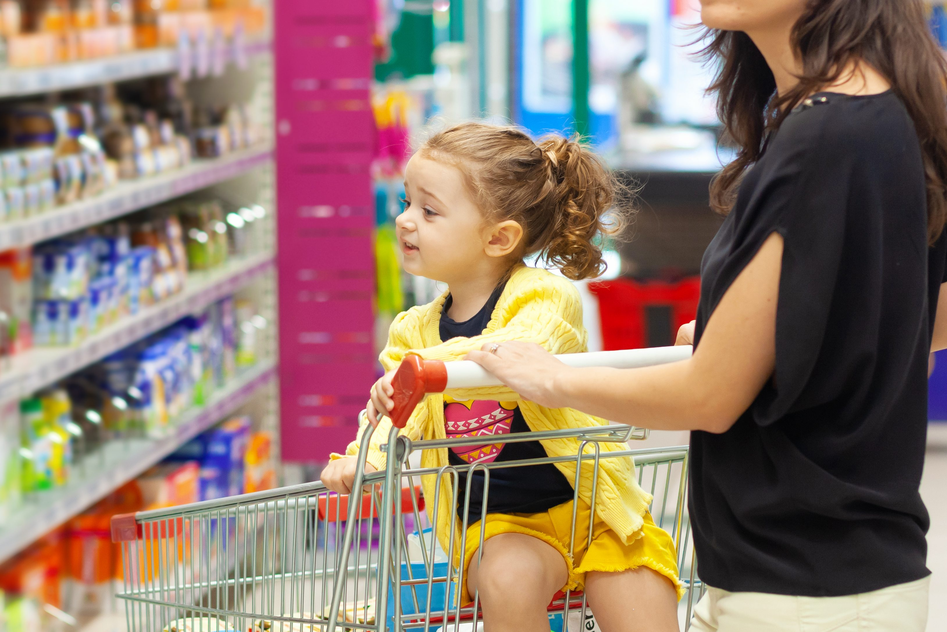 Child looks at grocery shelf selection from a shopping cart. (Shutterstock Image)