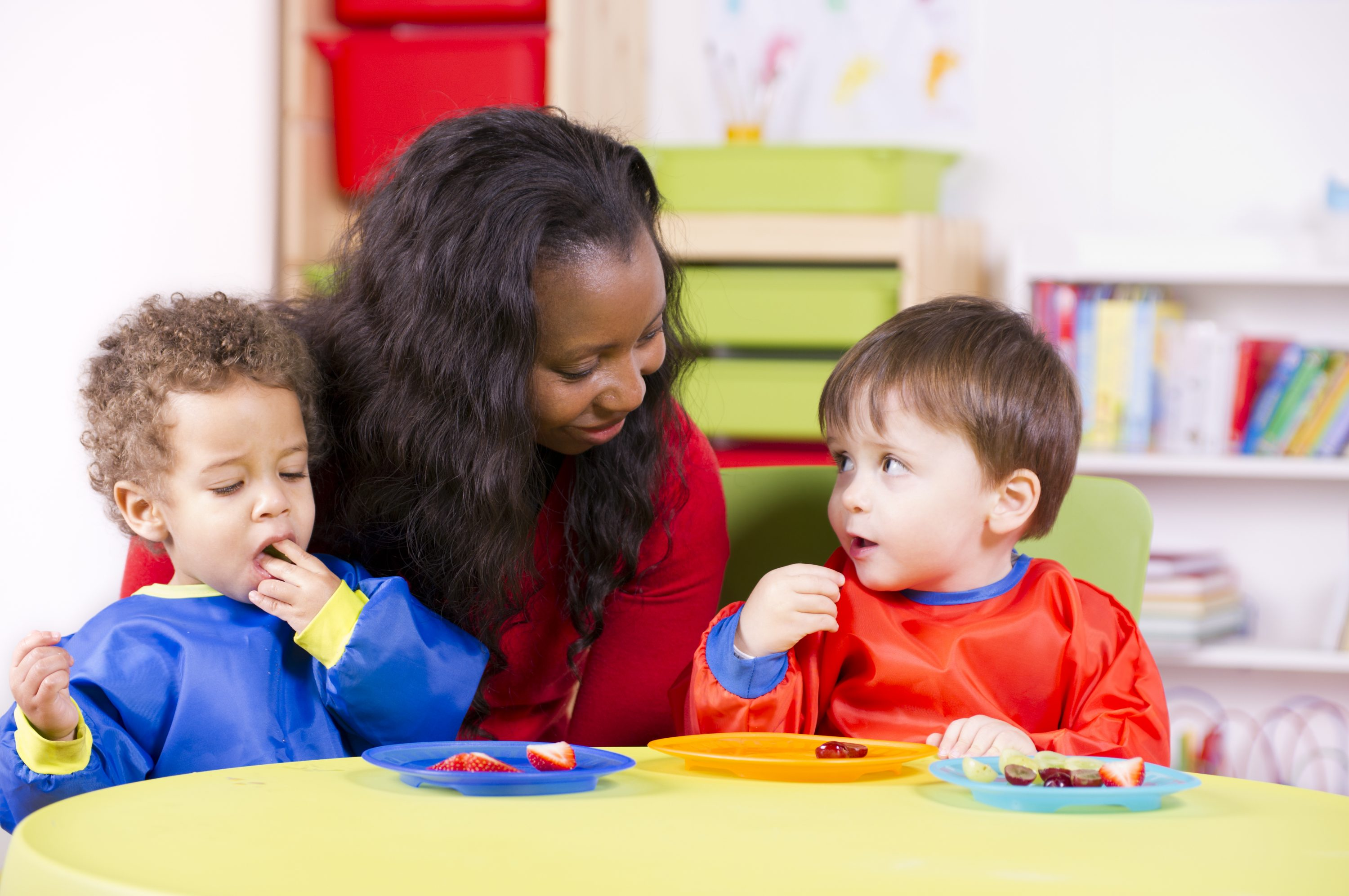 African American educator seated at table with two preschool aged children eating fruit