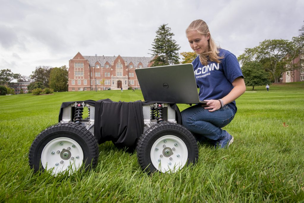 Emily Yale, one of the three inaugural students in the UConn Master's of Engineering in Global Entrepreneurship program, with her autonomous robot at the Great Lawn on Oct. 7. (Sean Flynn/UConn Photo)
