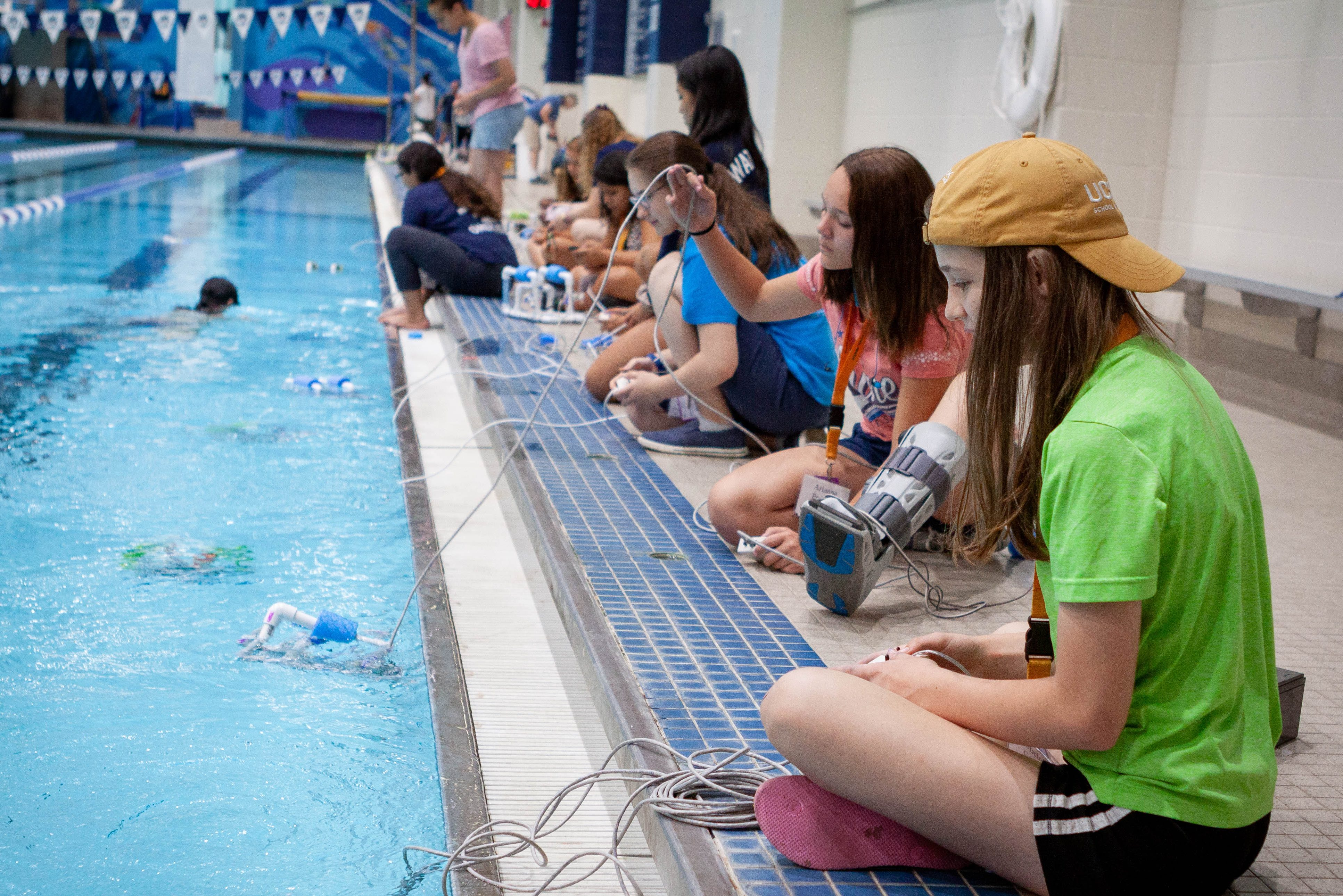 A group of SPARK campers work on their underwater robots in the UConn Wolff-Zackin Natatorium during the summer of 2019. SPARK seeks to mentor and encourage 7th-9th grade females to enter the STEM fields through overnight summer camps. (UConn Photo/Christopher LaRosa)