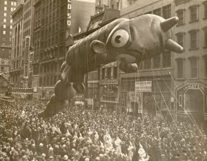 A black and white photo of a giant balloon in the Macy's Thanksgiving Day Parade in New York City