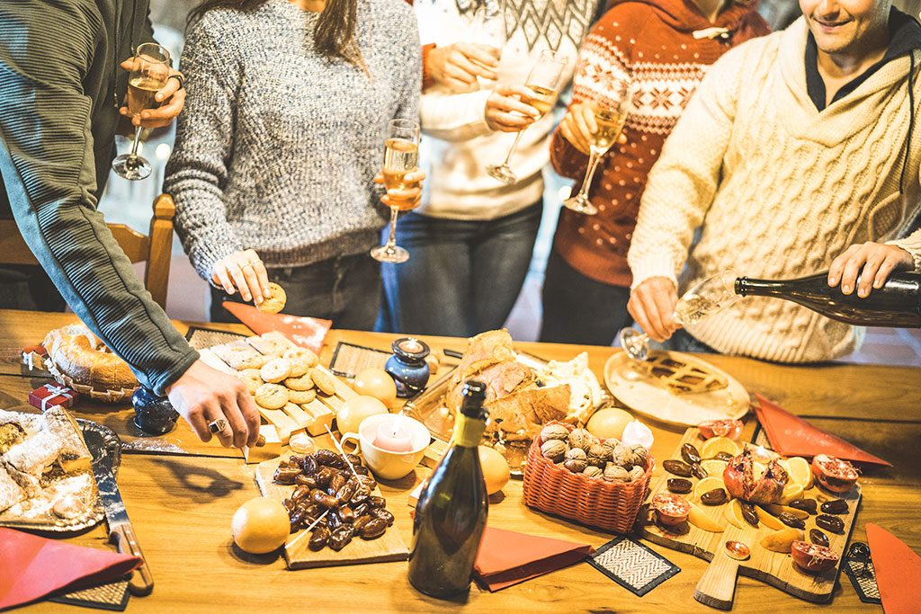 Party-goers with glass of wine in hand around snack table