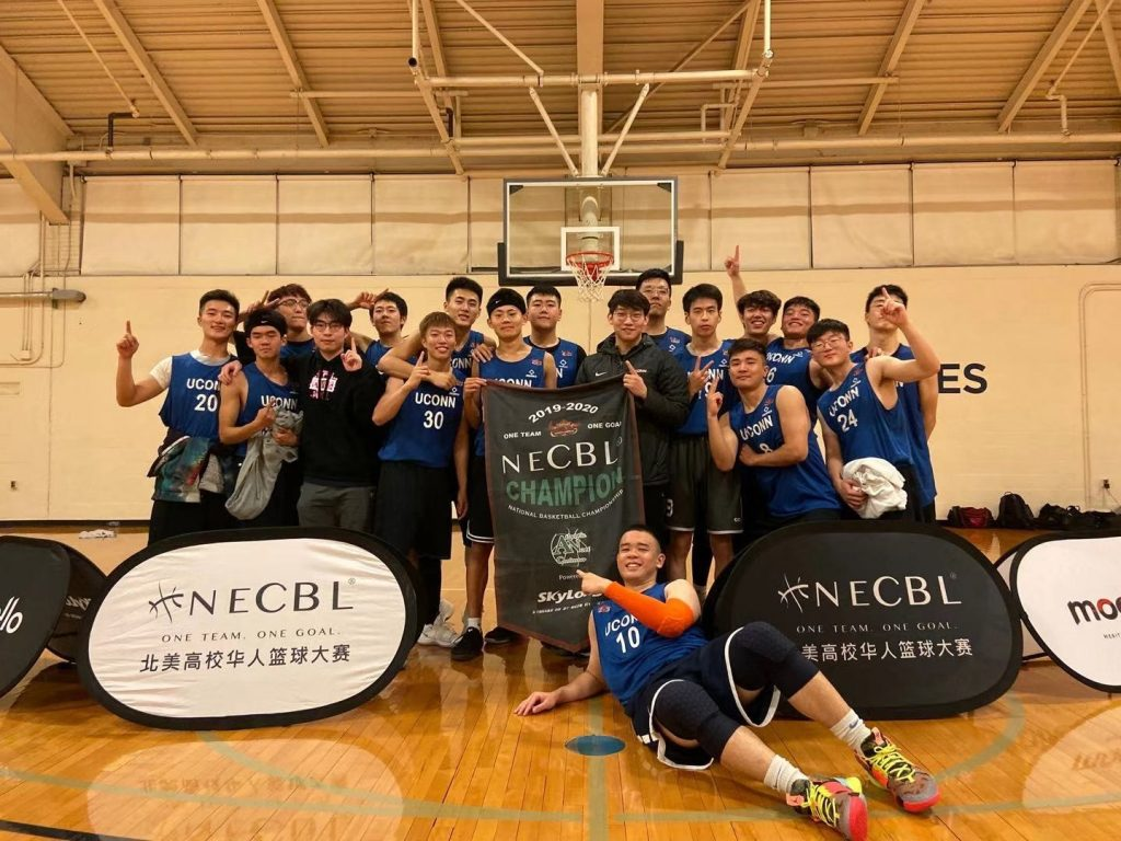 Members of the UConn Chinese Students and Scholars Association basketball team pose on a basketball court