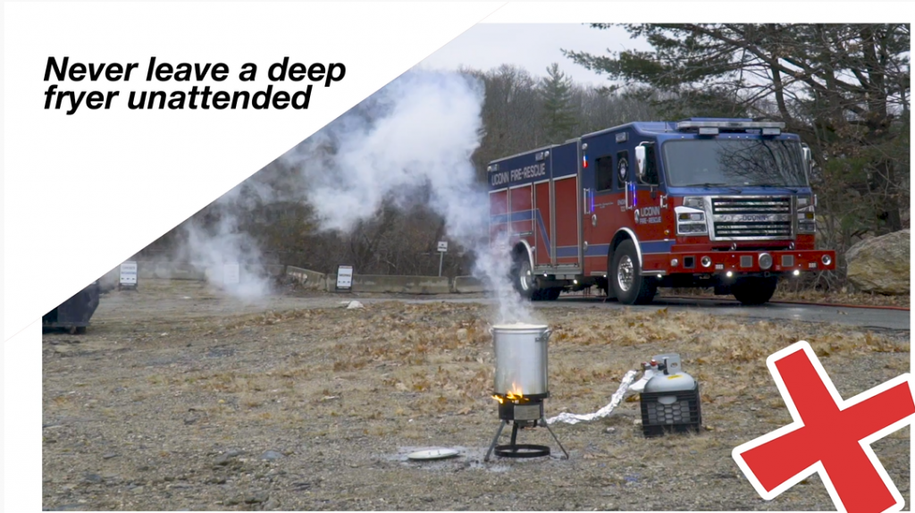 A deep fryer with a turkey inside burns while a UConn fire truck sits in the background.
