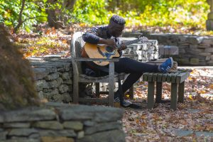 A student playing an acoustic guitar on a stone bench behind the Benton Museum of Art