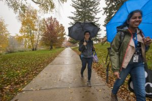 Students walking to class on a rainy fall day.