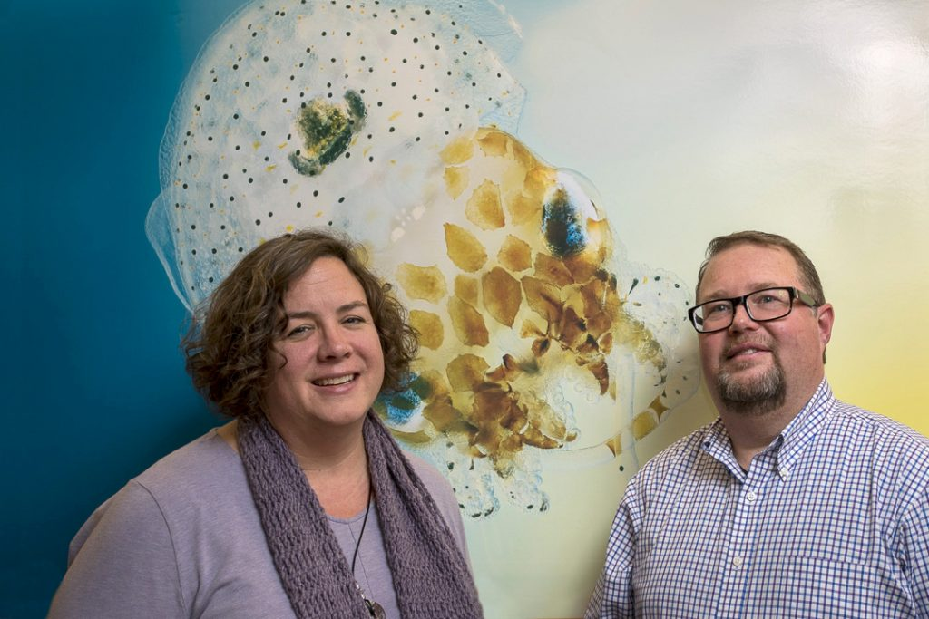 Researchers Marcy Balunas and Spencer Nyholm with a photo of a bobtail squid