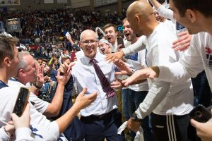 Coach Dan Hurley walks through a handshake line before a game at