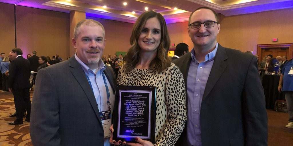 Kevin Chamberlin, Diana Sobieraj and William Baker at the ASHP Conference. Diana is holding a plaque for winning the 2019 Literary award