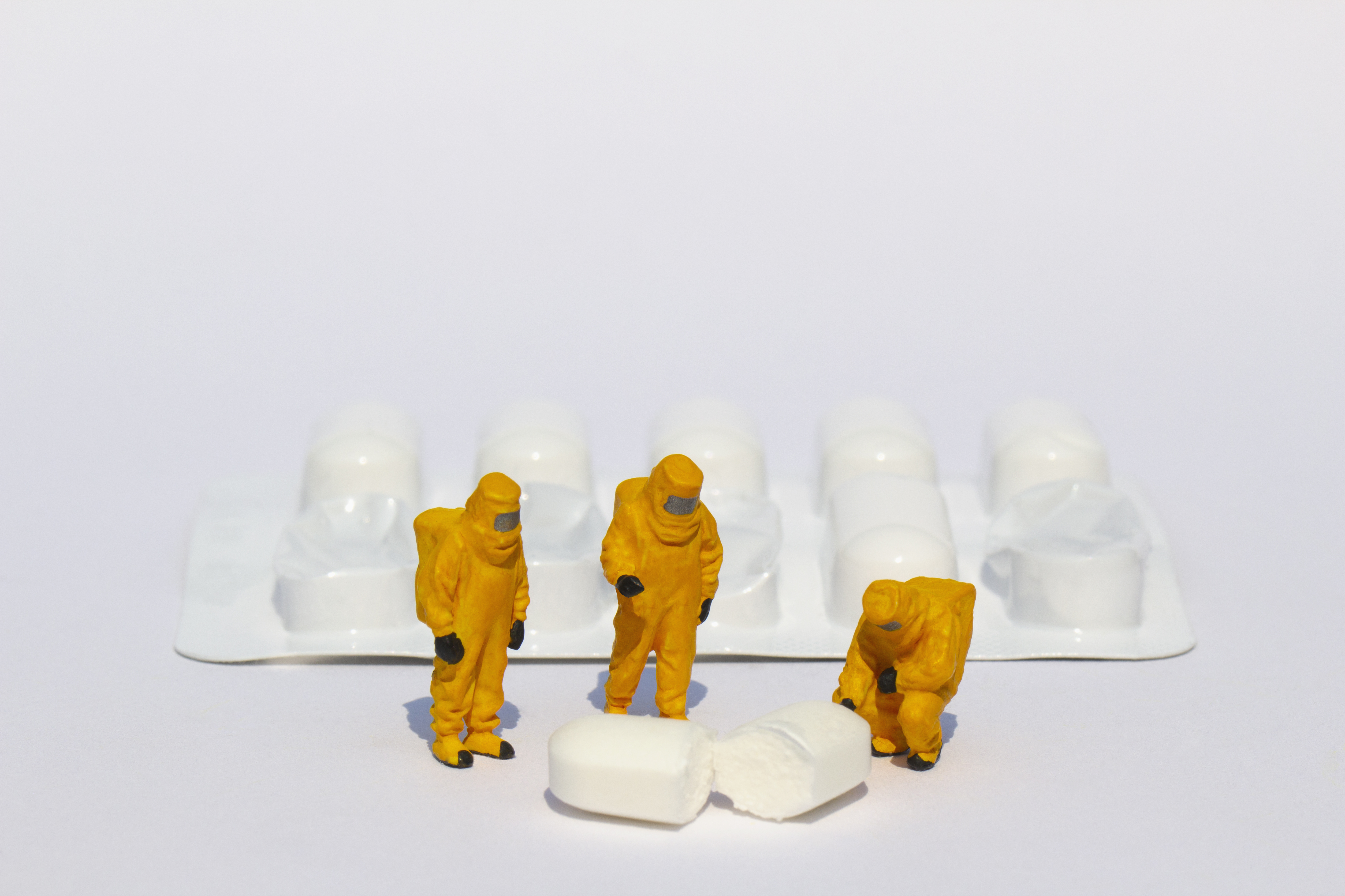 Tiny people in hazmat suits examining a prescription pill.