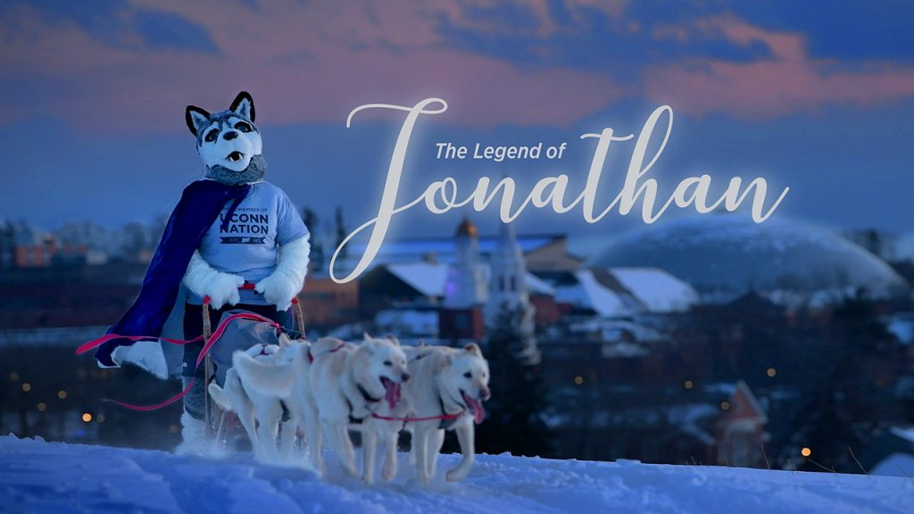 The costumed mascot Jonathan rides a sled pulled by real dogs on a snowy Horsebarn Hill.