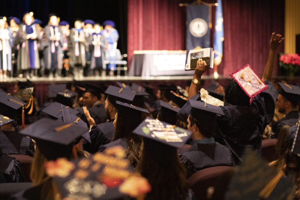 A UConn School of Nursing CEIN/BS graduate, sitting with her peers, facing the stage at the Jorgensen Center, raises her hands to cheer when her campus is announced.