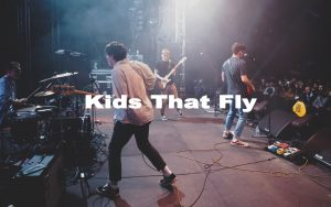 Members of the band Kids That Fly playing on stage.