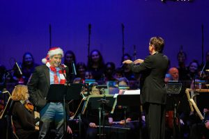 "President Thomas Katsouleas, left, reads ""A Visit from St. Nicholas"" by Clement Clarke Moore while Keith Lockhart conducts the Boston Pops at the Jorgensen Center for the Performing Arts on Dec. 14, 2019. (Peter Morenus/UConn Photo)"