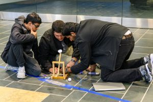 Three students crouched on the floor, working on a model for an engineering project.
