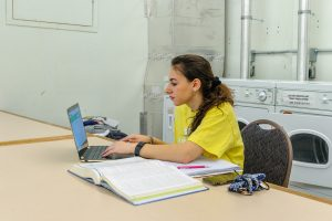 A student studies for a chemistry exam in the laundry room of a residence hall.