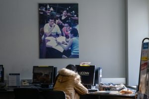 A student studies at Wilbur Cross beneath a picture of other students studying.