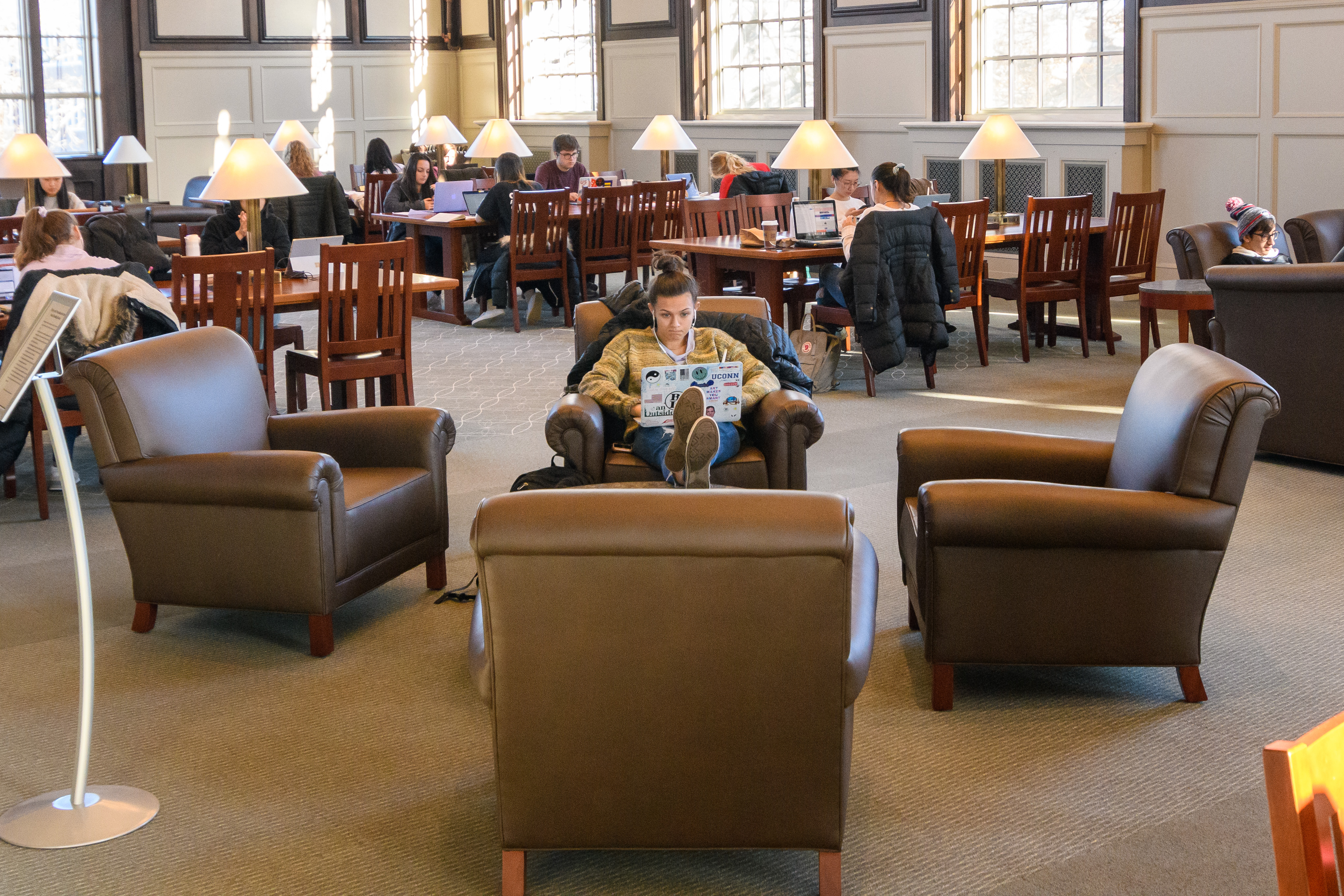 A student sits with her feet up while studying inthe Wilbur Cross South Reading Room.