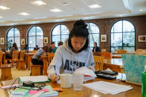 A student studies at a table, with papers spread out before her.