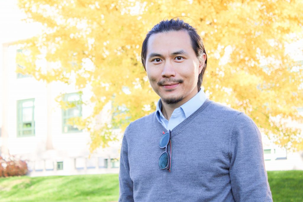 Dr. Zhe Zhu standing outside in front of a tree during autumn