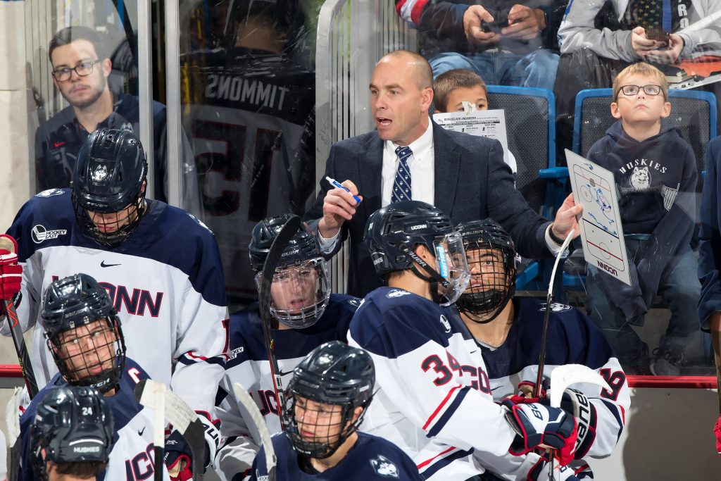 UConn men's ice hockey Coach Mike Cavanaugh on the bench during a game.
