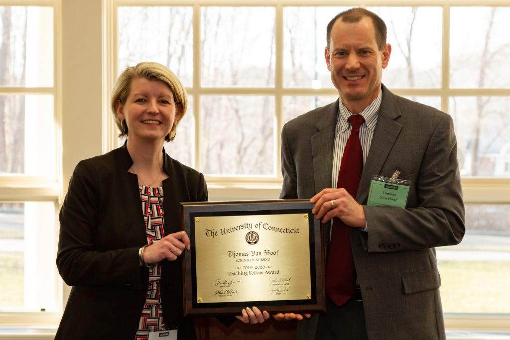 Anysley Diamond and Thomas Van Hoof hold an plaque honoring Van Hoof as a Center for Excellence in Teaching 2019-2020 University Teaching Fellow