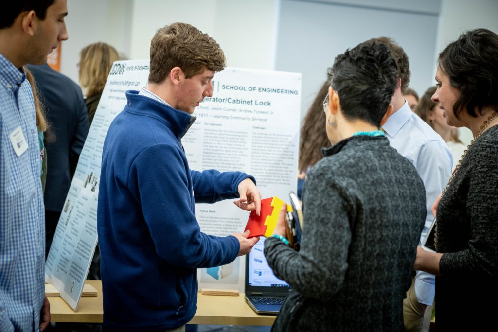 UConn Engineering students showcase a refrigerator lock during a poster session in December 2019. Students worked with UConn Service Learning Initiatives, WeHa Unified Business Club, and UConn Engineering House to come up with inventions designed to better meet the needs of people with autism and their families.