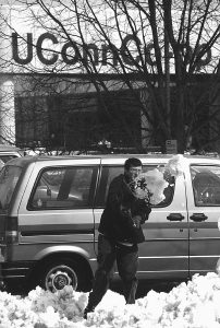 Jason Hall, a senior, shovels out his car on Fairfield Road after a 1997 snowstorm. This was shortly before Fairfield Road was closed to automobile traffic and became Fairfield Way.  (Peter Morenus/UConn File Photo)
