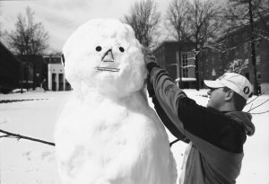 Freshman Mike Kapareiko puts the finishing touches on a snowman outside North Campus after a 1997 storm that dumped more than a foot of snow on Storrs. (Peter Morenus/UConn File Photo)