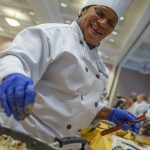 Chef Lucinda Simms adding ingredients to a pan at the Culinary Olympics on Jan. 14, 2020. (Sean Flynn/UConn Photo)
