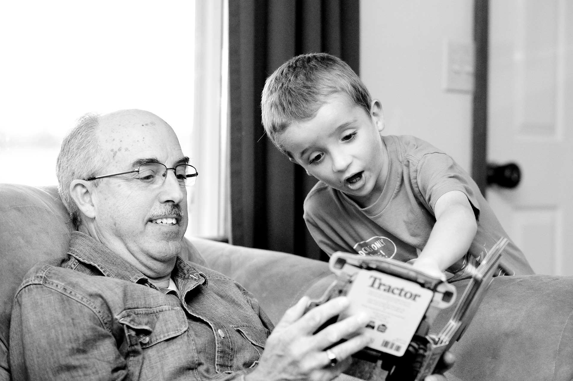 Black and white photo of an older man sitting on a couch holding a book, while a young boy looks on.