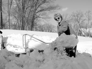 A black and white photo from the 1990s shows a woman shoveling snow on campus.