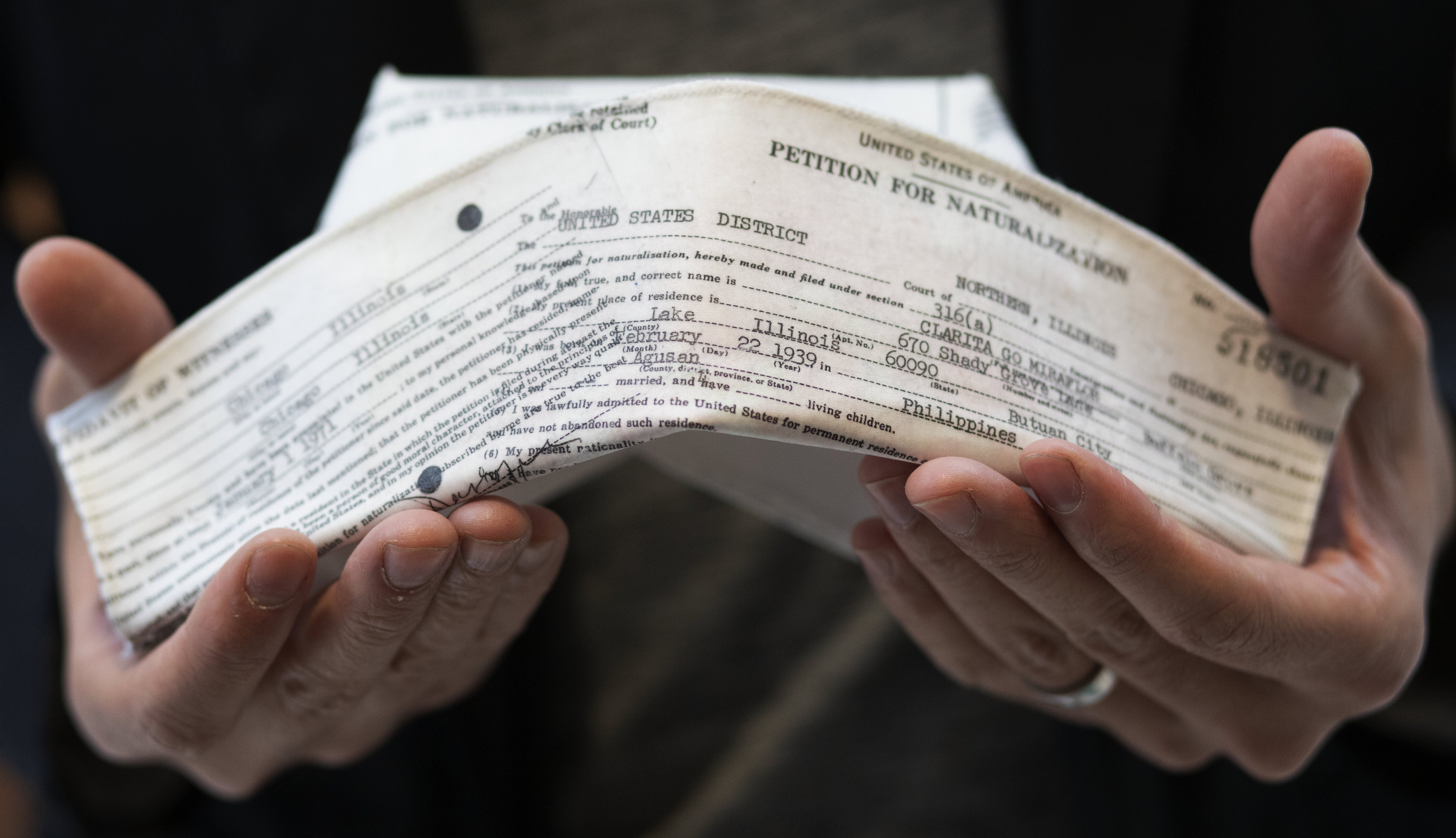 A traditional white nurses' cap is imprinted with the type-written text of an immigration and naturalization form. It it held in a man's hands in this close-up image.