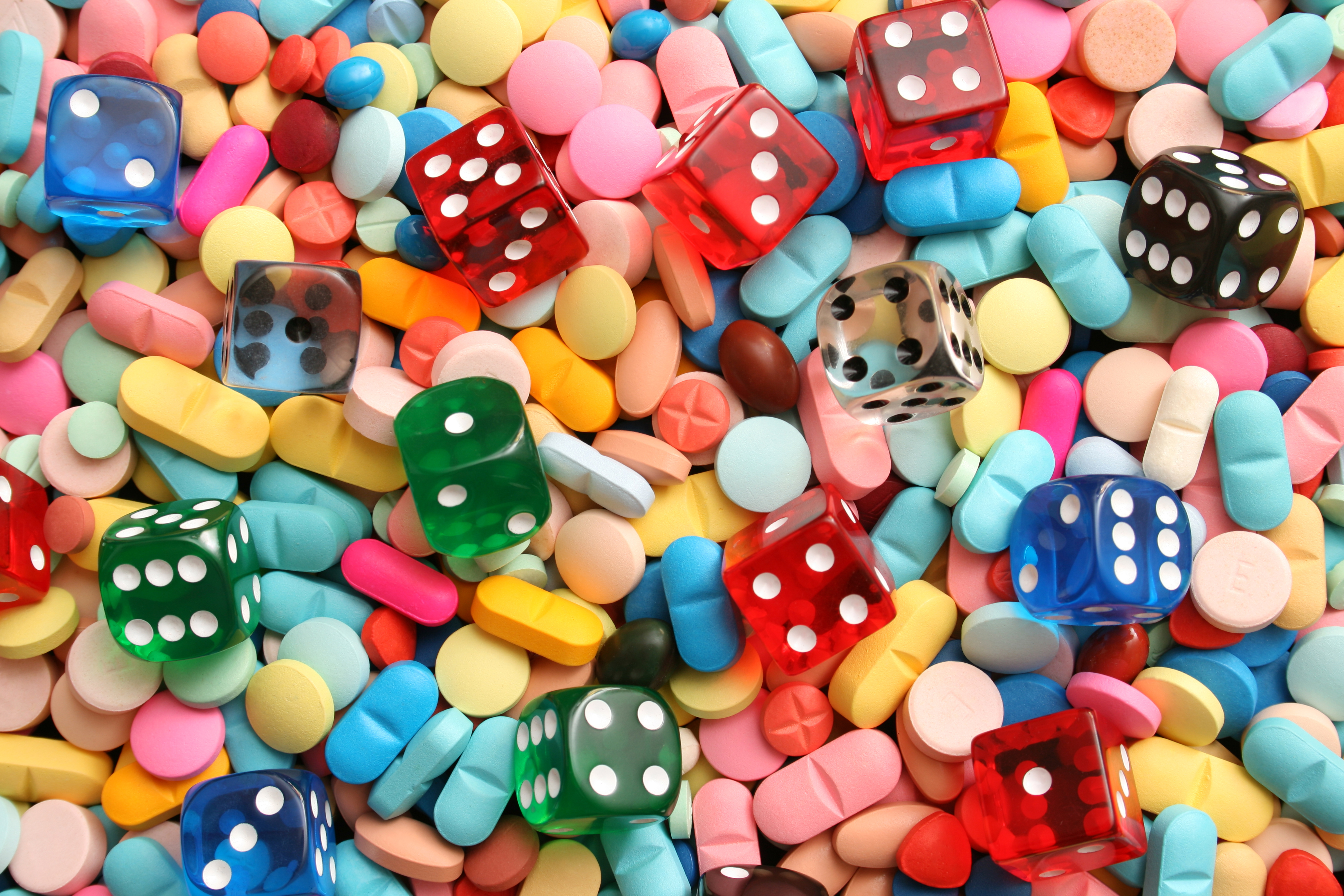 A multicolored array of pills, mixed in with dice to illustrate the risk of untested dietary supplements.