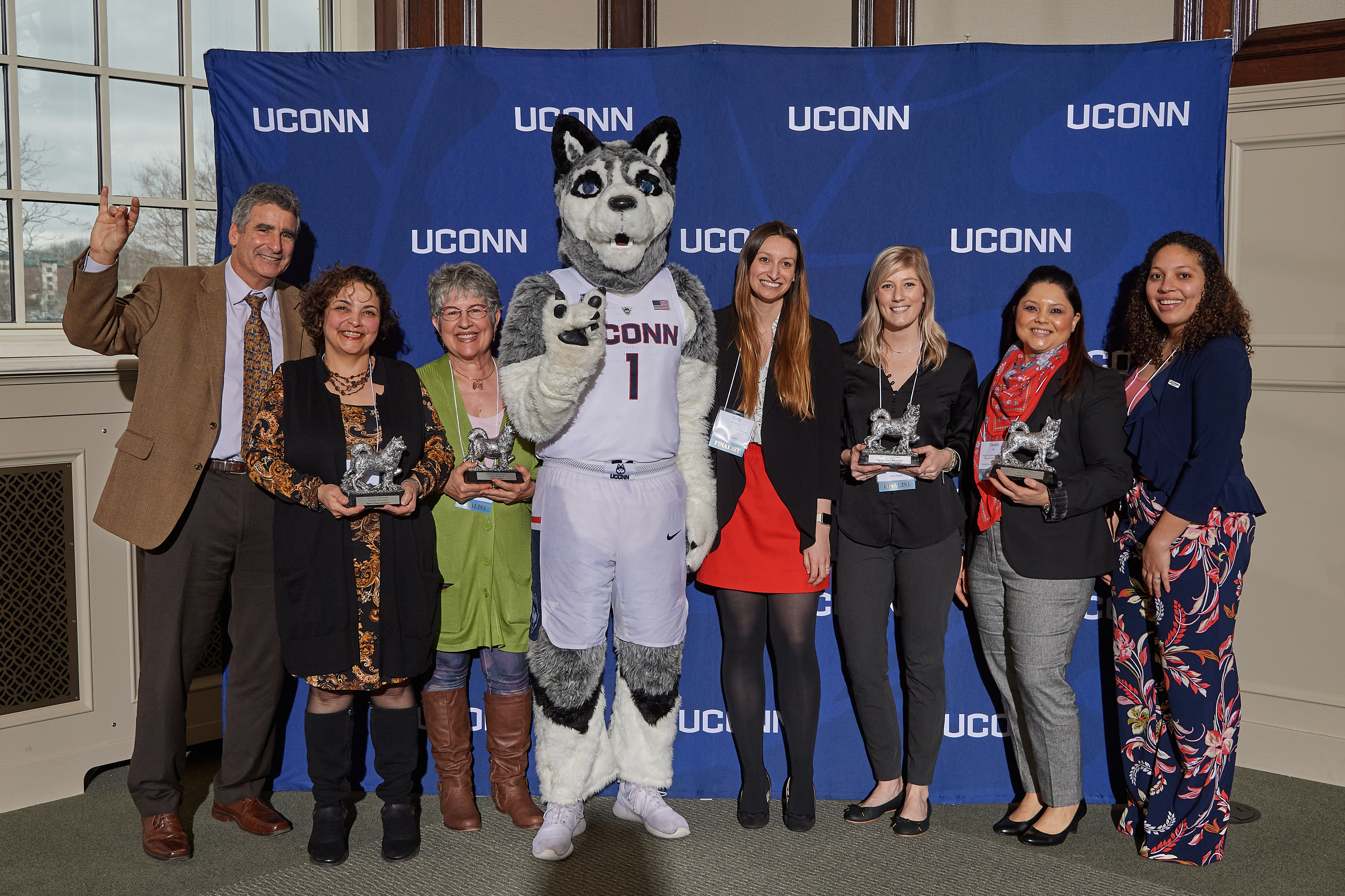 President Tom Katsouleas and Jonathan the Husky pose with 2020 UConn Spirit awards recipients at the Wilbur Cross North Reading Room