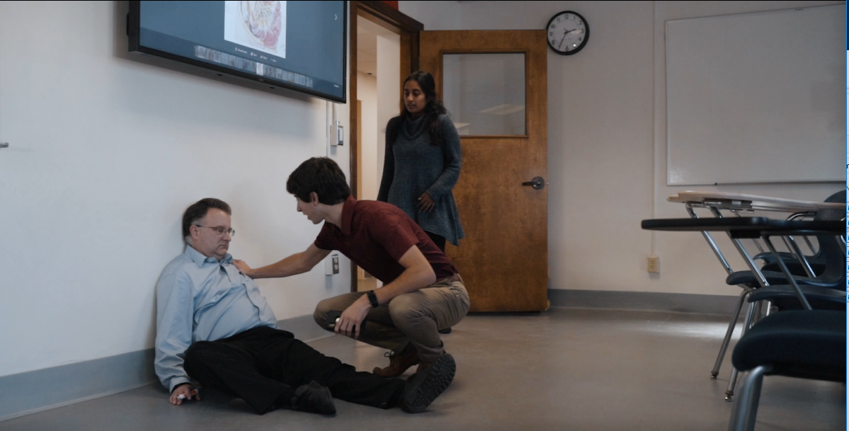 In a still from a training video, students discover an unconscious man sitting on the floor.