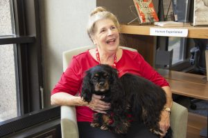 Dr. Karen Obadowski with her Cavalier King Charles spaniel on her lap in the Health Sciences Library