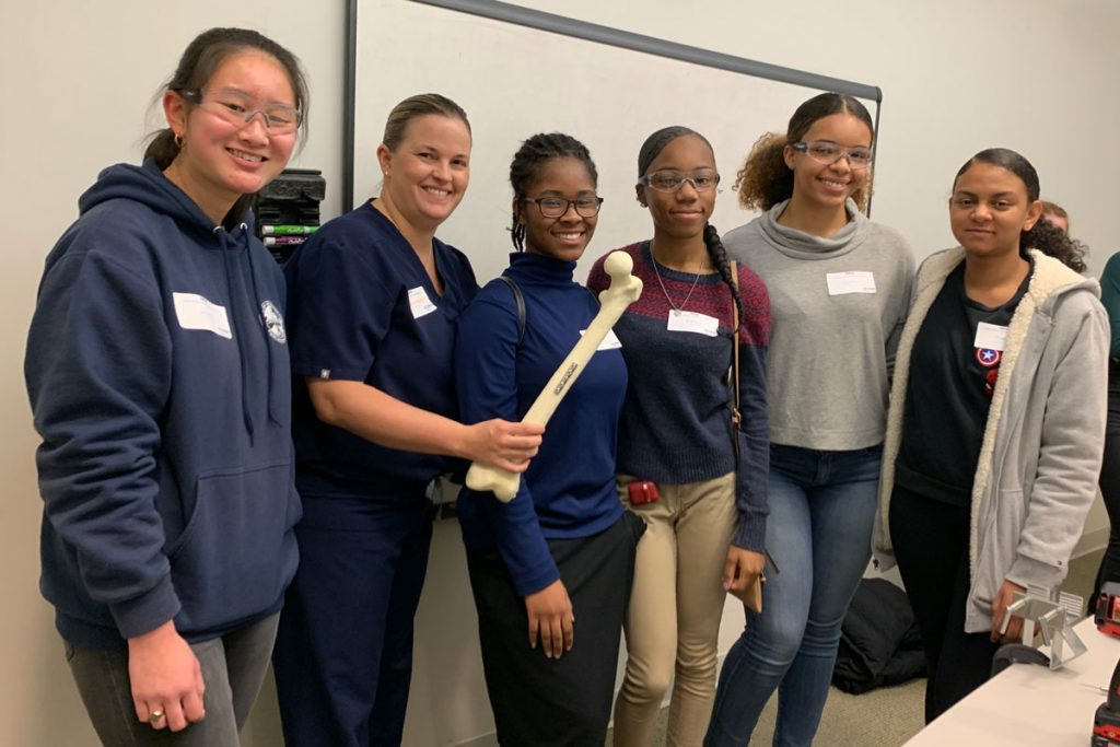 High school students with Dr. Katherine Coyner, who holds a repaired bone model.