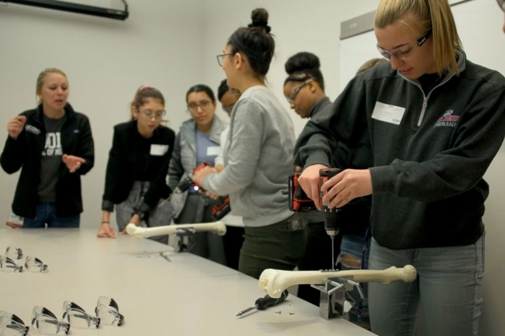 Six students and an instructor, two students with drills working on bone model repair
