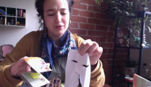 MFA student Felicia Cooper, a graduate assistant at the Ballard Institute and Museum of Puppetry, shows the paper puppet and mask she made during an online video that can be found at the Ballard website. (Photo courtesy Ballard Institute and Museum of Puppetry)