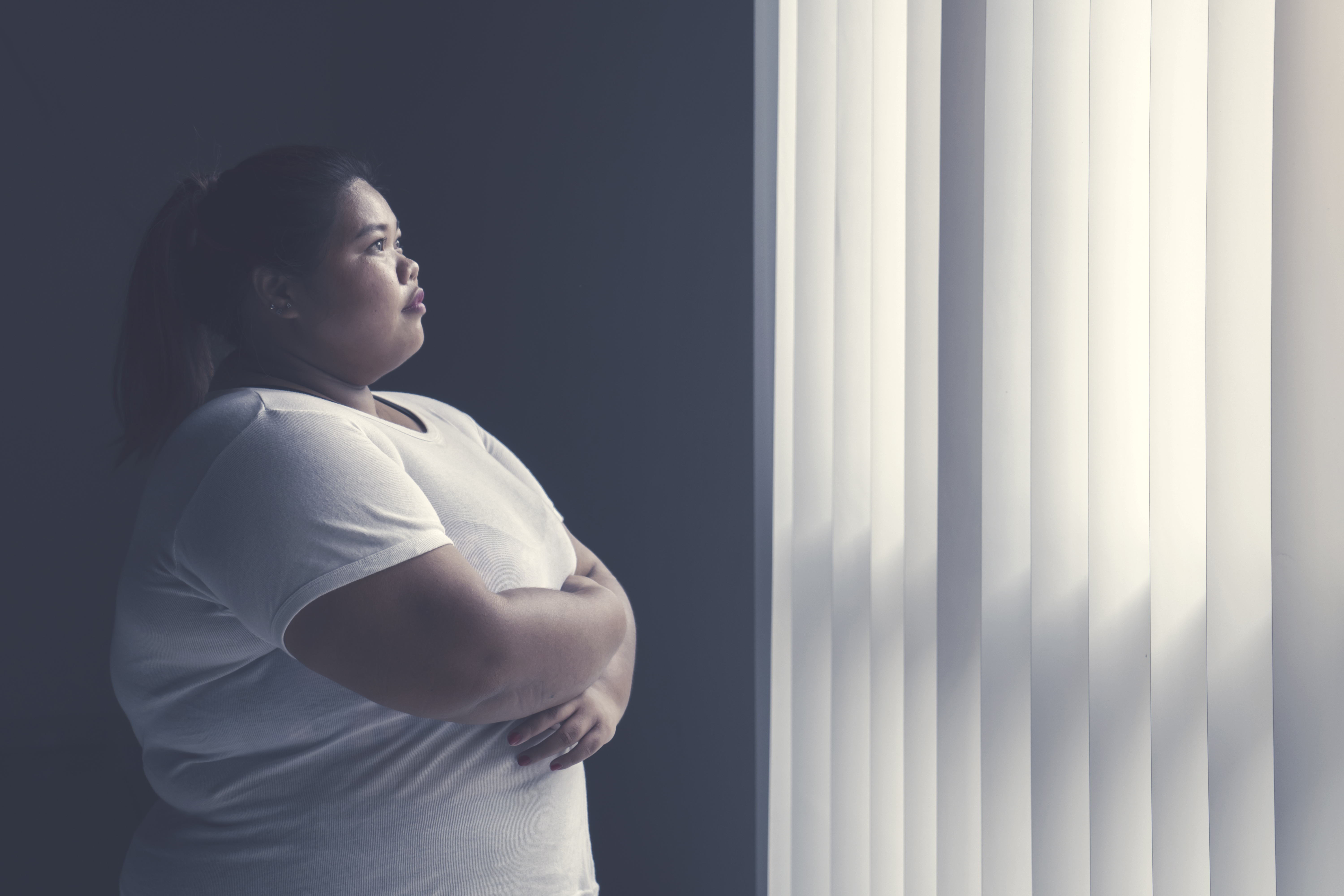 An overweight woman looks out a window